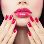 Makeup Lips with Pink Glossy Lipstick and Pink Nails. Shiny Lips and Hand with Manicure