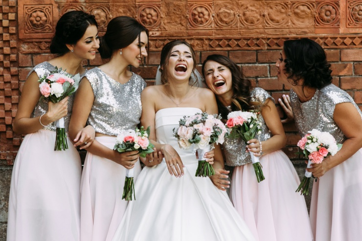 Cute bridesmaids and a bride are laughing